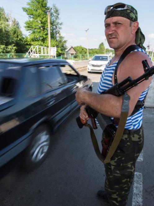 An armed pro-Russian separatist guards a border post abandoned by Ukrainian border guards at...