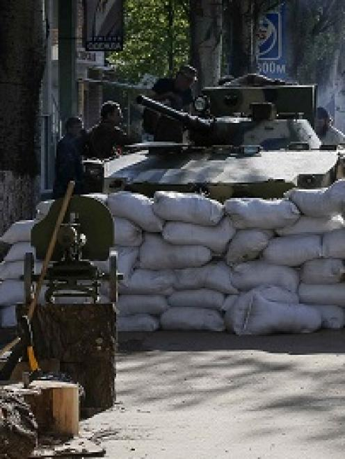 An armoured personnel carrier is seen near a barricade around the state security service building...