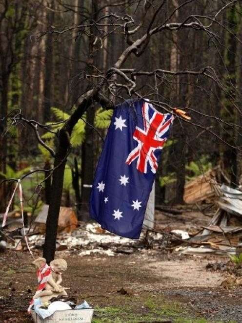 An Australian flag hangs from a tree in Marysville, Victoria on the three-month anniversary of...