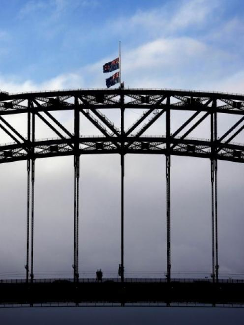An Australian national flag and a New South Wales state flag (top) fly at half-mast atop the...