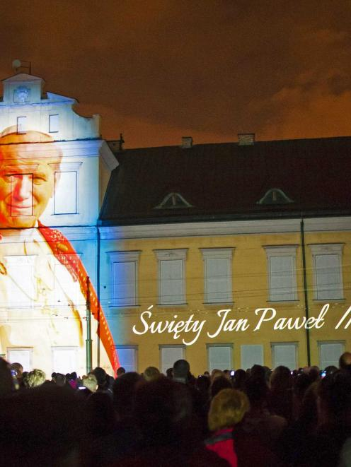 An image of Pope John Paul II is projected during a multimedia show a night before his...