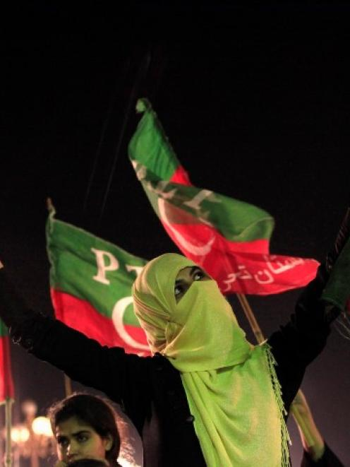 An Imran Khan supporter cheers while listening to him speak during what has been dubbed a ...