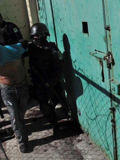 An inmate is escorted by riot policemen after a gunfight in the Tuxpan prison in Iguala. REUTERS...