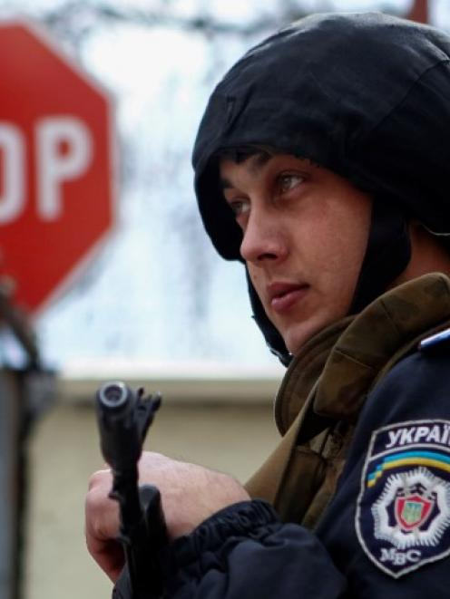 An Interior Ministry member stands guard at an Ukrainian Interior Ministry base in Donetsk....