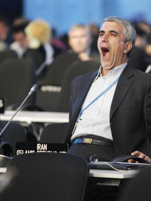 An Iranian delegate fights boredom during a plenary session of the UN Climate Change Conference ...