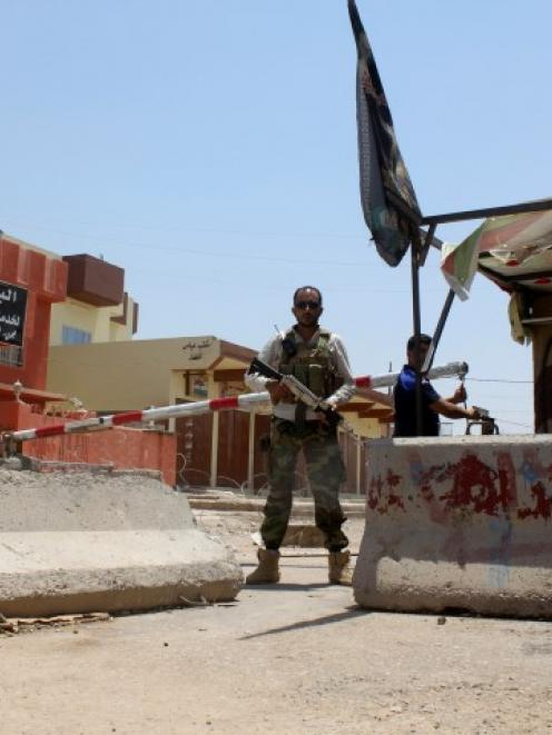 An Iraqi Shi'ite Turkmen fighter stands guard at a checkpoint at Tuz Khurmato in Salahuddin...