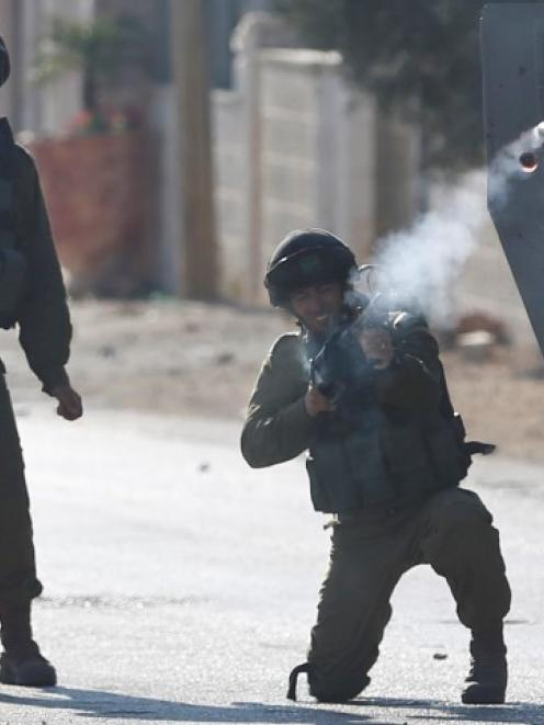 An Israeli soldier fires a tear gas canister at Palestinian protesters following a protest...