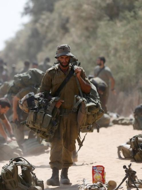 An Israeli soldier from the Givati brigade carries his gear after returning to Israel from Gaza....