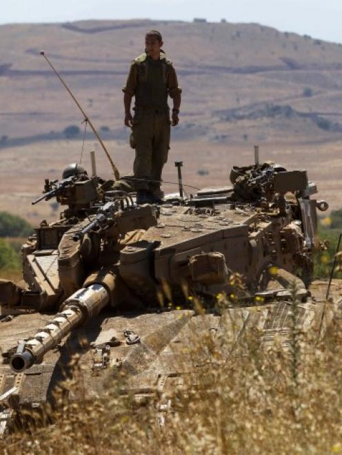An Israeli soldier stands atop a tank near Alonei Habashan on the Israeli occupied Golan Heights,...