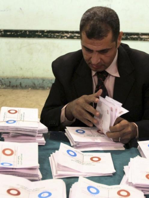 An official counts ballots after polls closed in Bani Sweif, about 115km south of Cairo. Photo by...