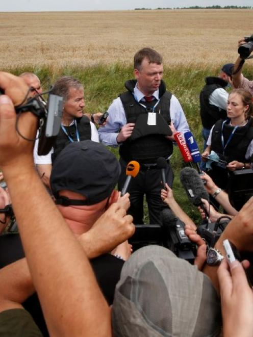 An Organisation for Security and Cooperation in Europe monitor speaks to journalists at the crash...