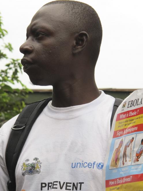 An outreach worker holds a poster bearing information on the symptoms of Ebola virus disease (EVD...