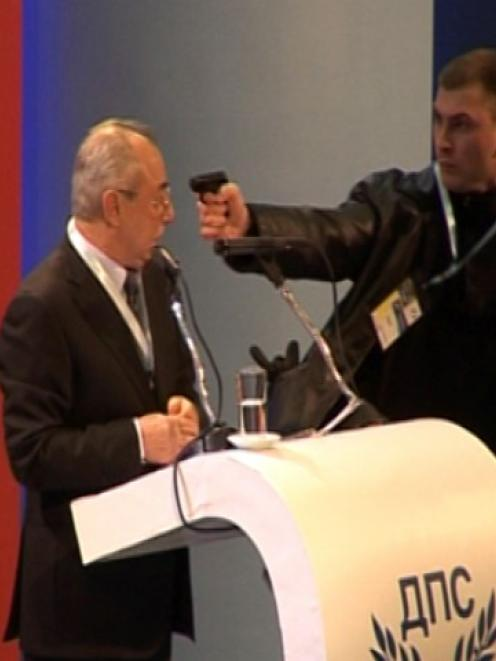 An unidentified man levels a gun at Ahmed Dogan, leader of Bulgaria's Movement for Rights and...