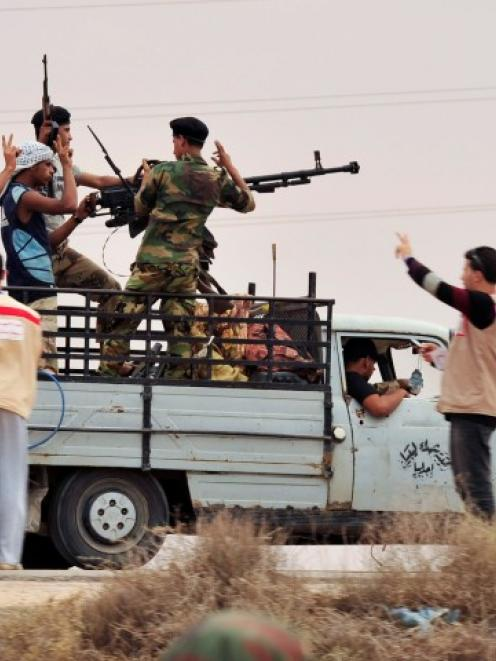 Anti-Gaddafi fighters flash victory signs behind an anti-aircraft gun as they take up position...