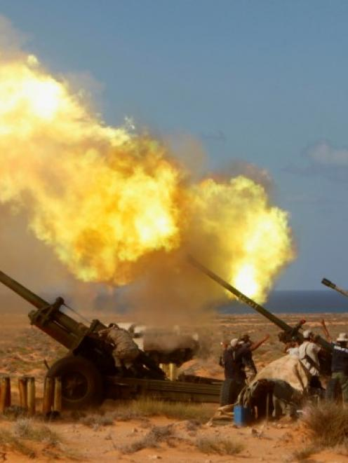 Anti-Gaddafi forces fire a Howitzer at the artillery line in Om El Khanfousa, Libya. Photo:...