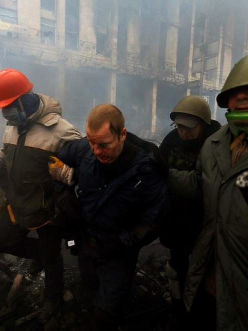 Anti-government protesters detain a policeman (2nd L) during clashes in the Independence Square...
