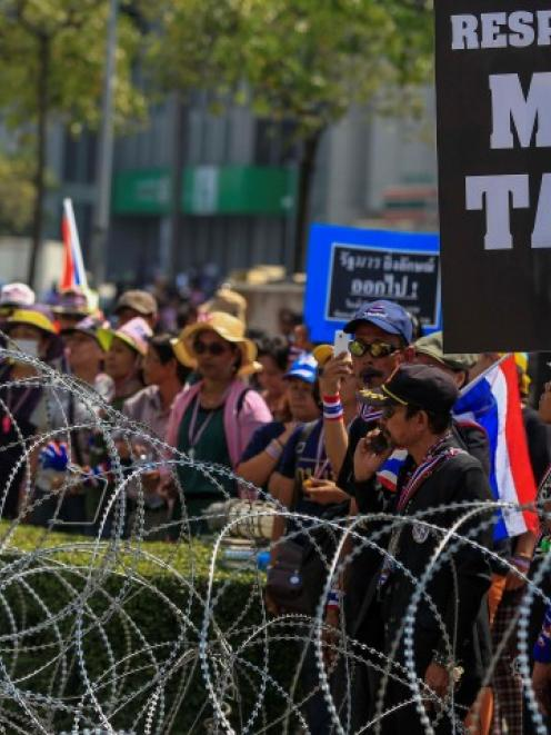 Anti-government protesters gather near a barbed-wire fence at a government office where Prime...