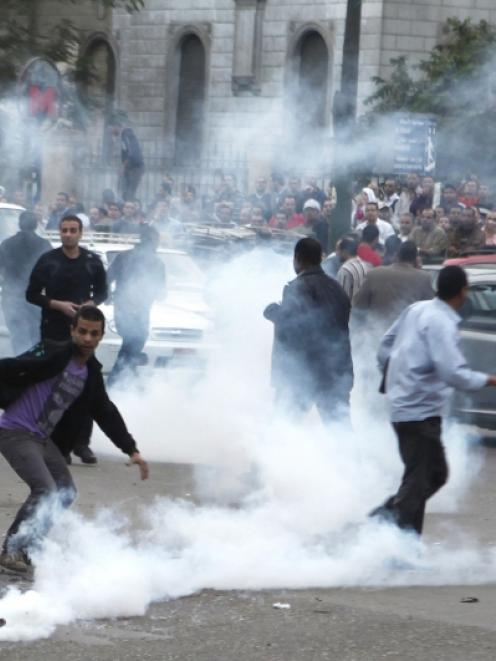 Anti-Mursi protesters run from tear gas released by police during clashes in front of the Supreme...