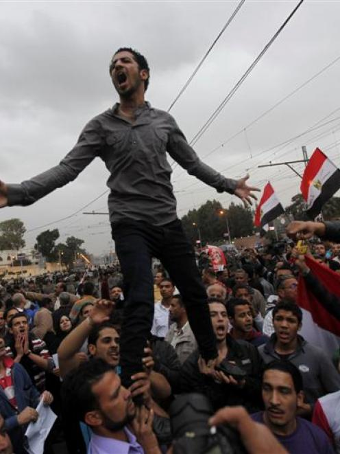 Anti-Mursi protesters shout slogans during a protest in front of the presidential palace in Cairo...