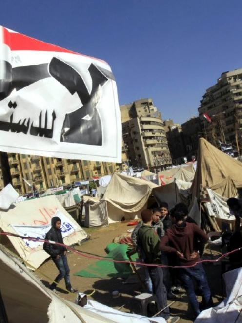 Anti-Mursi protesters sit outside their tents, below a flag that reads 'No, to Constitution' at...