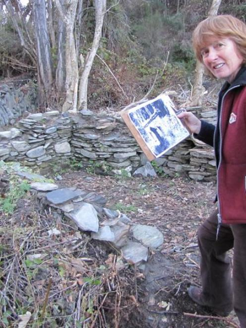 Archeological artist Jan Morrison, of Arrowtown, holds an archive picture of the stone...
