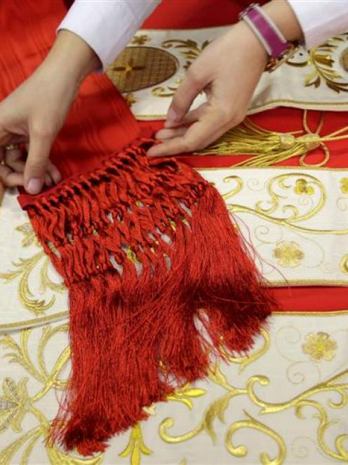 Arianna, Mario's Musa daughter, adjusts a stole over cardinal cassocks at her father's ...