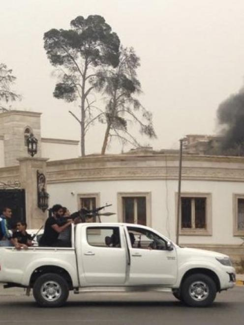 Armed men aim their weapons from a vehicle as smoke rises near the General National Congress in...