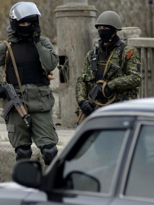 Armed men stand at an improvised checkpoint in Slaviansk. Pro-Russian separatists have set up...