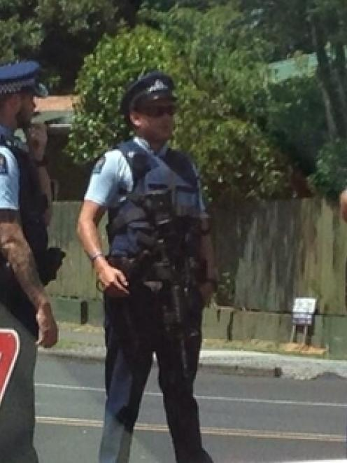 Armed police lock down an area of Takanini yesterday after the carjacking at gunpoint.