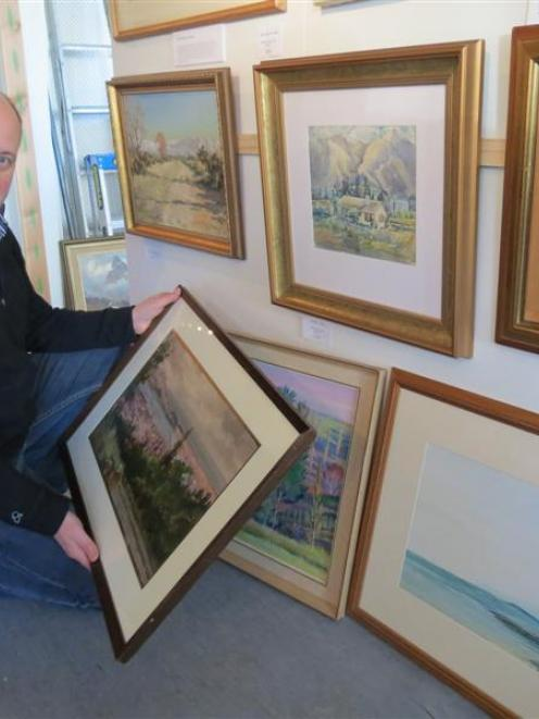 Arrowtown Gallery manager Simon Beadle admires newly released original artworks by  deceased...