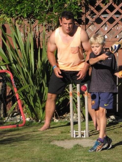 Arrowtown junior rugby player Johnny Ffisk (9) bats one-handed during a game of backyard cricket...