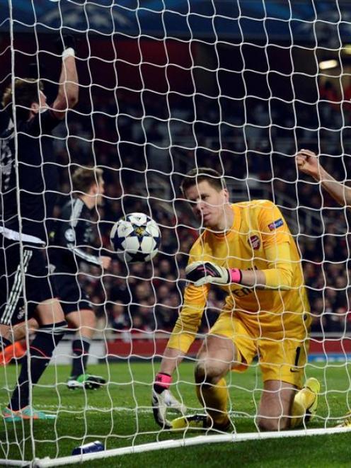 Arsenal's goalkeeper Wojciech Szczesny reacts as Bayern Munich's Mario Mandzukic and Thomas...