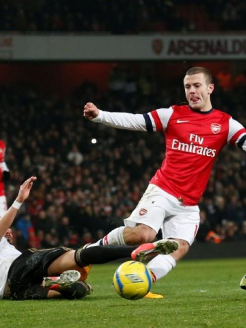 Arsenal's Jack Wilshere (2nd R) is challenged by Swansea City's Chico Flores and Ashley Richards,...