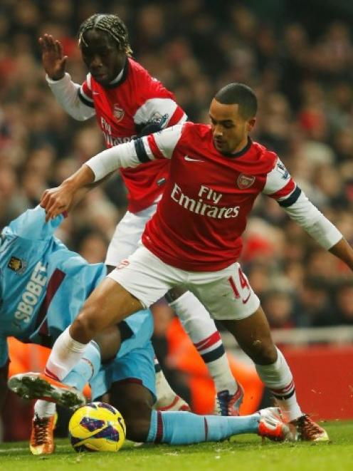 Arsenal's Theo Walcott (R) is challenged by West Ham's Carlton Cole during their English Premier...