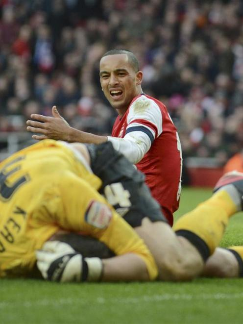 Arsenal's Theo Walcott reacts after a collision with Blackburn's Jake Kean. REUTERS/Philip Brown