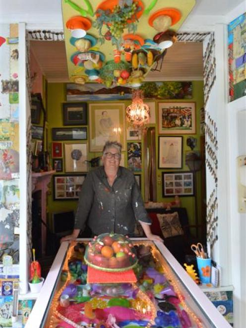 Artist Janet de Wagt beneath the upside-down dinner setting in her lounge. Photo by Gerard O'Brien.