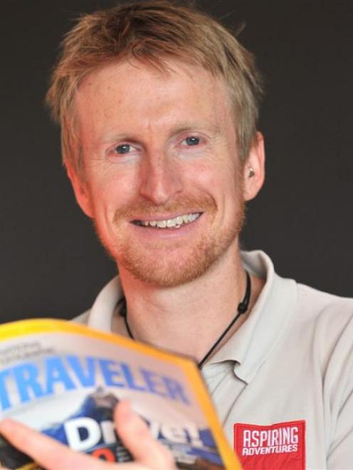 Aspiring Adventures co-founder Steve Wilson, with a copy of National Geographic Traveler magazine...
