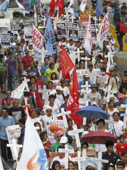 At a rally in Manila last month, protesters display placards and crosses bearing the names of...