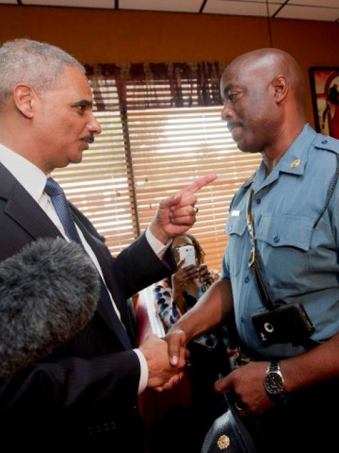 Attorney General Eric Holder talks with Capt. Ron Johnson of the Missouri State Highway Patrol at...