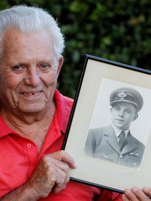 Aubrey Bills (91) holds a photograph of himself in uniform as a 20-year-old, while recounting a...