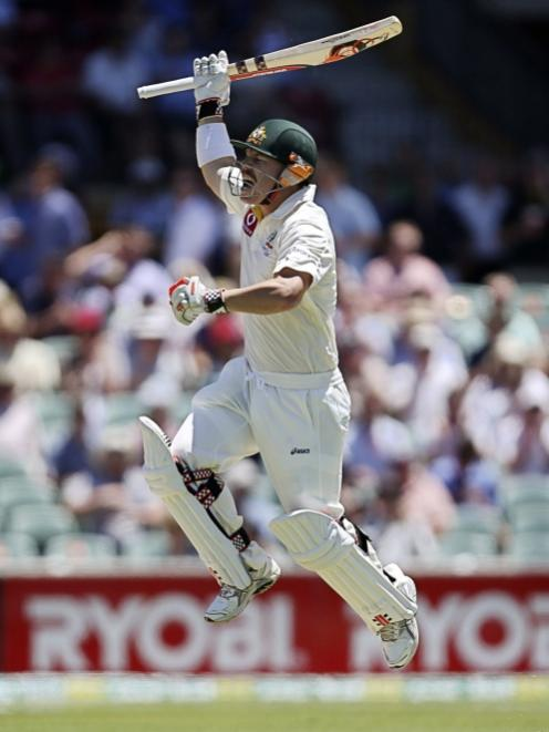 Australia's David Warner celebrates scoring a century during their second cricket test match...