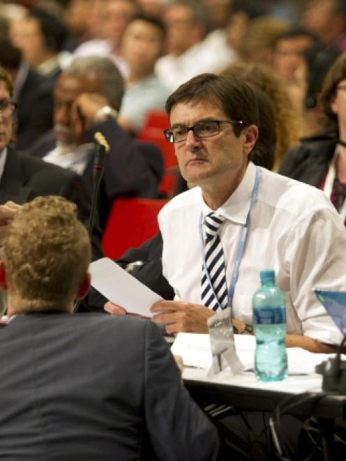 Australia's Minister for Climate Change Greg Combet speaks with other delegates during a break in...