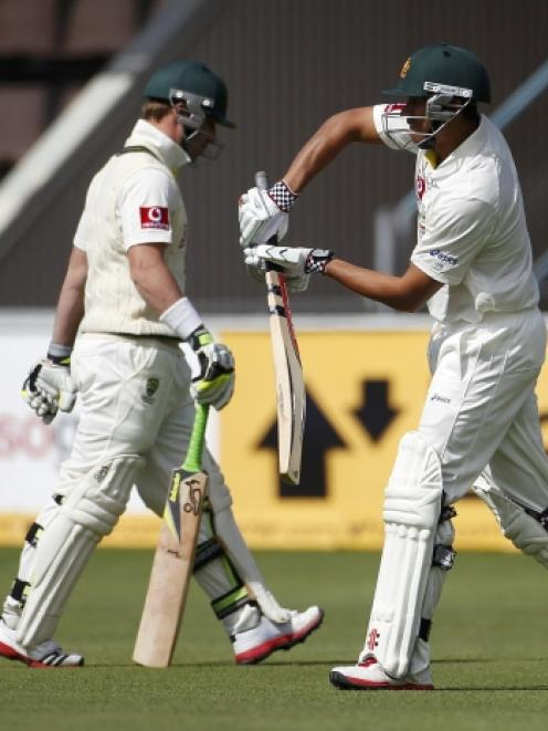 Australia's Phil Hughes (L) passes incoming batsman Usman Khawaja after he was dismissed by New...