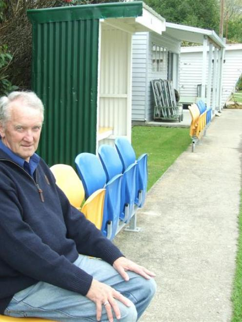 Balclutha Bowling Club secretary Graham Dale sits on a row of  salvaged plastic Carisbrook seats...