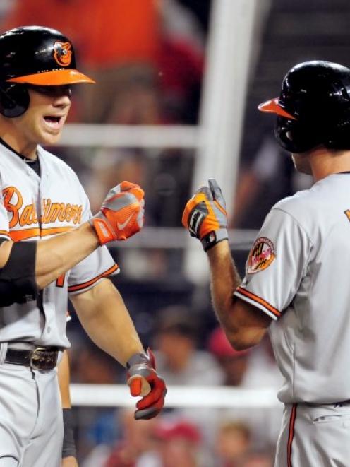 Baltimore Orioles first baseman Chris Davis (19) fist bumps shortstop J.J. Hardy after hitting a...