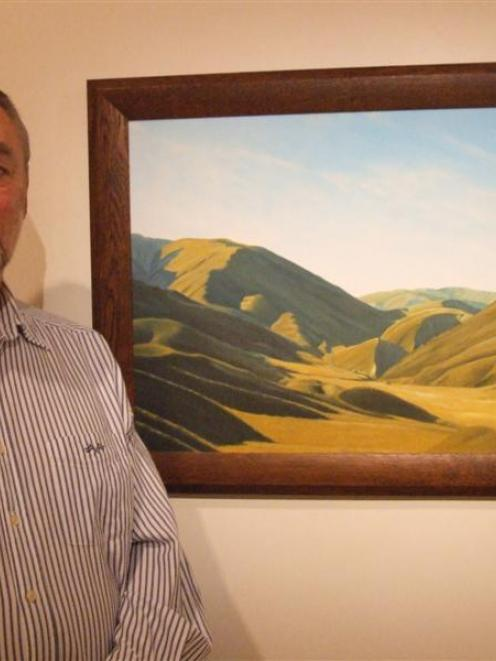 Barry Mackenzie with a painting of the Lindis Pass which is part of his exhibition at the...