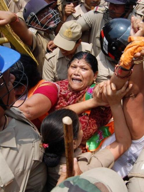 Bharatiya Janata Party supporters are stopped by police from moving towards the office of...