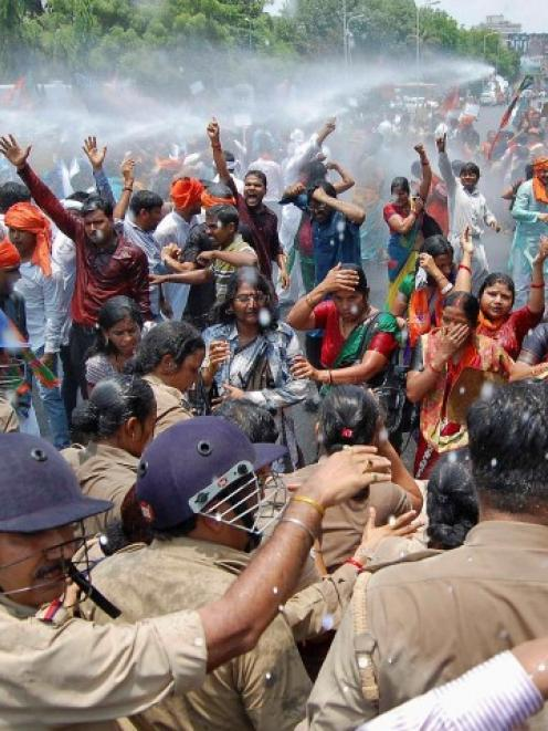 Bharatiya Janata Party supporters shout slogans as police use a water cannon to stop them from...