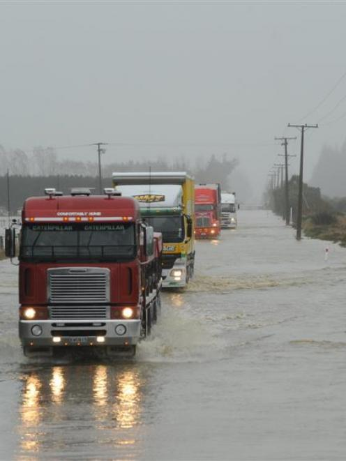 Big trucks negotiate flooding on State Highway 1 north of Oamaru in late May. Photo by Stephen...