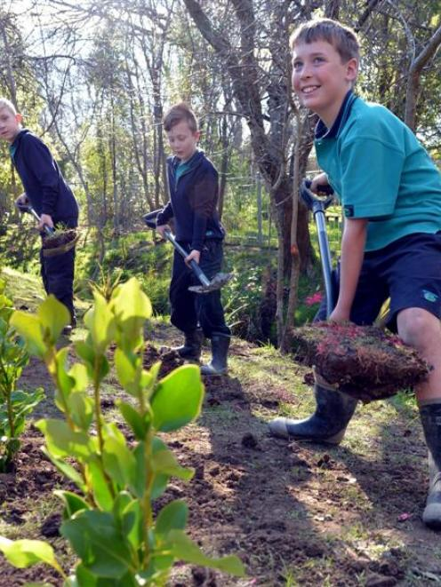 Blake Conroy (9, left), Liam Wilson (10, centre) and Devin Colston (10) plant trees at East...